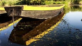 漂浮在湖的划艇和在它反射 库存图片