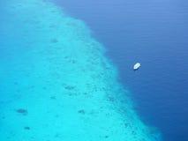 漂浮在珊瑚礁附近的旅游渡轮鸟瞰图 免版税库存图片