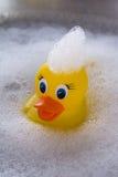 漂浮在肥皂suds的黄色橡胶鸭子 免版税库存图片