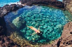 漂浮在自然水池的妇女 免版税库存图片