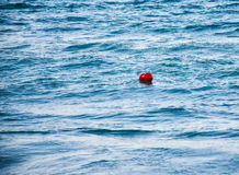 漂浮在蓝色海的红色浮体挥动 免版税库存照片