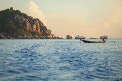 漂浮在蓝色海的长尾巴小船在酸值nang元和酸值t 库存图片