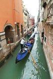 漂浮在运河的长平底船的Ourists在威尼斯 免版税库存图片