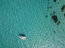 漂浮在透明海的一条被停泊的小船的鸟瞰图 免版税图库摄影