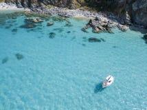 漂浮在透明海的一条被停泊的小船的鸟瞰图 免版税库存照片