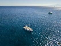 漂浮在透明海的一条被停泊的小船的鸟瞰图 图库摄影
