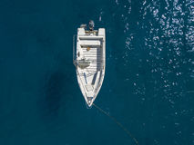 漂浮在透明海的一条被停泊的小船的鸟瞰图 库存照片