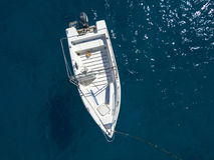 漂浮在透明海的一条被停泊的小船的鸟瞰图 库存图片