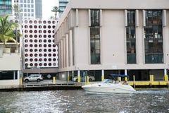 漂浮在都市风景背景的水表面上的汽船 免版税库存图片