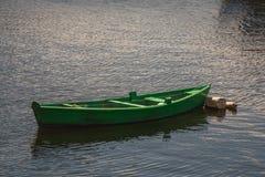 漂浮在镇静水的绿色单一小船 库存图片