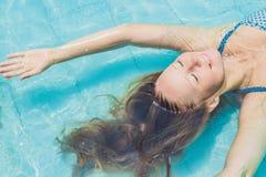漂浮在水池松弛顶视图的美丽的少妇 节假日概念 图库摄影
