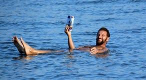 漂浮在死海的咸水的中人们 免版税库存图片