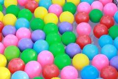 漂浮在水的五颜六色的塑料球 免版税库存图片