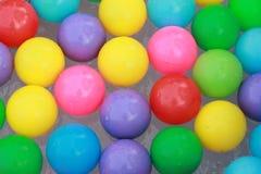 漂浮在水的五颜六色的塑料球 免版税库存照片