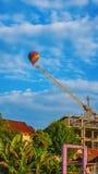 漂浮在建筑用起重机的位置的五颜六色的热空气气球 免版税图库摄影
