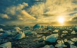 漂浮在Jokulsarlon的冰山在与glac的日落金黄小时 免版税库存照片