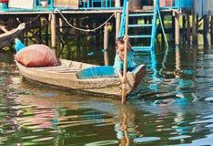 漂浮在Tonle Sap湖的小船的一个未认出的男孩 免版税库存照片