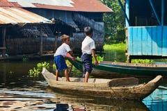 漂浮在Tonle Sap湖的小船的未认出的男孩 库存照片