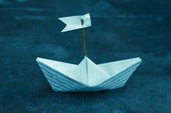 漂浮大海表面上的一条白皮书小船 免版税库存图片