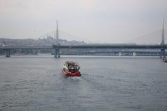 漂浮对金黄垫铁地铁桥梁的快速的红色小船 免版税库存照片