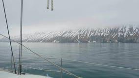 漂浮通过多雪的山的帆船在海洋,从船板的看法 影视素材