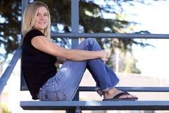 漂白剂白肤金发的坐的妇女 免版税库存照片