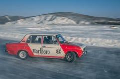 漂移在冰的白色和红色汽车 图库摄影