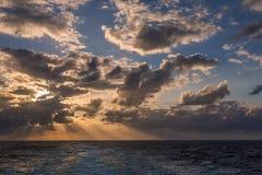 漂移在加勒比海的热带水的剧烈的套云彩在白天之前的最后片刻点燃 免版税库存照片