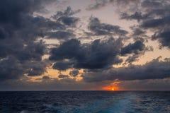 漂移在加勒比海的热带水的剧烈的套云彩在白天之前的最后片刻点燃 库存照片