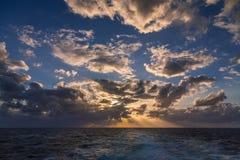 漂移在加勒比海的热带水的剧烈的套云彩在白天之前的最后片刻点燃 图库摄影