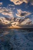 漂移在加勒比海的热带水的剧烈的套云彩在白天之前的最后片刻点燃 库存图片