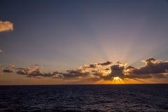 漂移在加勒比海的热带水的剧烈的套云彩在白天之前的最后片刻点燃 免版税库存图片