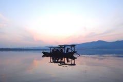 漂移在日落的一个湖的中国木小船 免版税库存照片