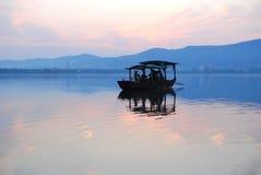 漂移在日落的一个湖的中国木小船 库存图片