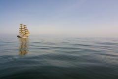 漂移在风平浪静海的双桅船 图库摄影