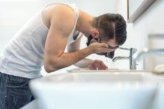漂洗他的面孔的有胡子的人在卫生间里 免版税库存照片