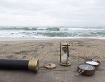 滴漏、小望远镜和指南针在海的背景 免版税库存照片