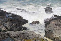 漏在多岩石的海滩上的波浪 免版税库存图片