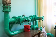漏的有毛病的阀门,适合在管道桶在它下在工厂工厂中 概念:管子和阀门修理与 免版税图库摄影