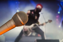 演出有一个吉他弹奏者的话筒后面模糊的背景的 摇滚明星概念 免版税库存照片