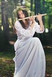 演奏一支长笛的美丽的妇女在森林 库存照片