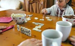 演奏与她的家庭的女孩多米诺 免版税库存照片