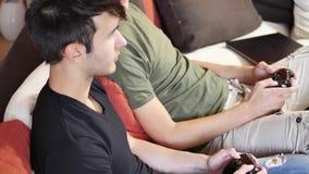 演奏与控制杆的年轻朋友计算机游戏 影视素材