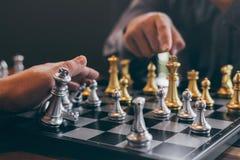 演奏与相反队的聪明的商人下棋比赛竞争,计划的事务战略对胜利的发展 图库摄影