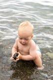 演奏与石头的愉快的小孩 逗人喜爱的男婴获得乐趣在黑海 免版税库存照片