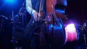 演奏与钢琴演奏家的音乐家低音提琴背景特写镜头的 供以人员在阶段黑暗的艺术家戏剧木低音提琴 影视素材