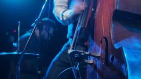 演奏与钢琴演奏家的音乐家低音提琴背景特写镜头的 供以人员在阶段黑暗的艺术家戏剧木低音提琴 股票录像