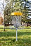 演奏与链子的篮子在公园机智的投掷的飞盘的 库存图片