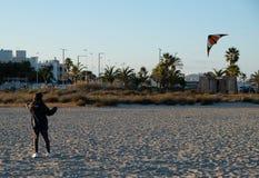 演奏与风筝n海滩的女孩在冬天季节期间在日落-时间概念 库存图片