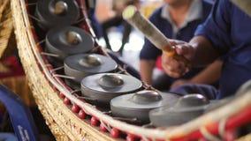演奏与鼓槌的泰国鼓手音乐在传统金属锣打鼓在寺庙的仪器 4K,慢的关闭 股票视频